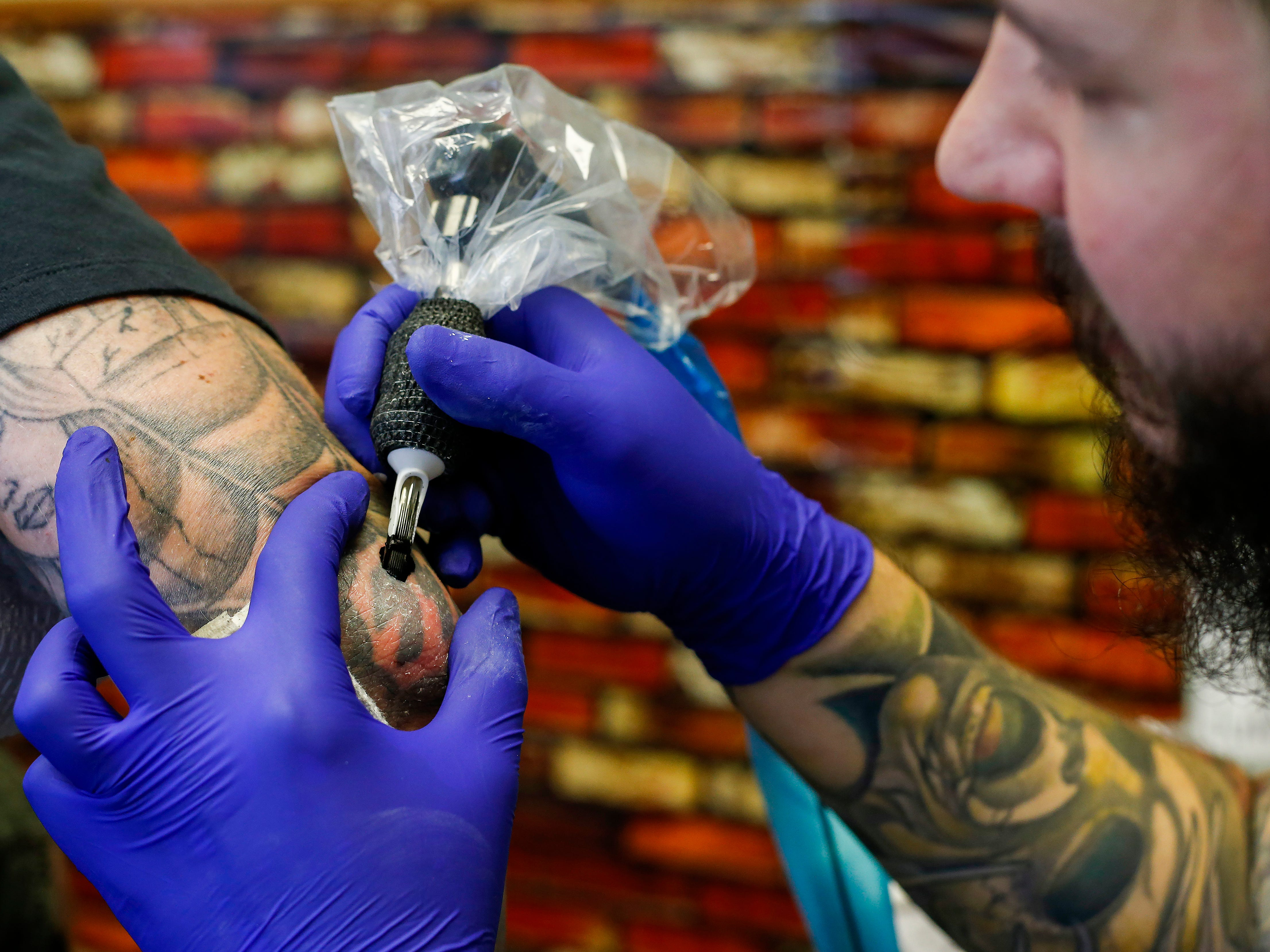 Justin Fleetwood, a tattoo artist at Queen City Tattoo Company, begins to cover up a Nazi SS bolt tattoo on the elbow of a man who wished not to be identified on Tuesday, Aug. 21, 2018. Fleetwood is offering to cover up people's hate-tattoos at no cost.