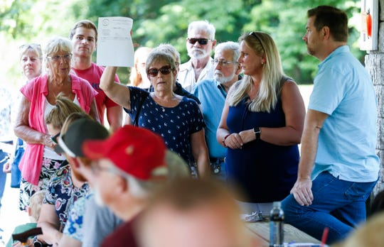 Vivian Short holds up a comment card for residents to fill out as she speaks during a meeting with developers of a proposed apartment complex near Sequiota Park on Tuesday, Aug. 21, 2018.