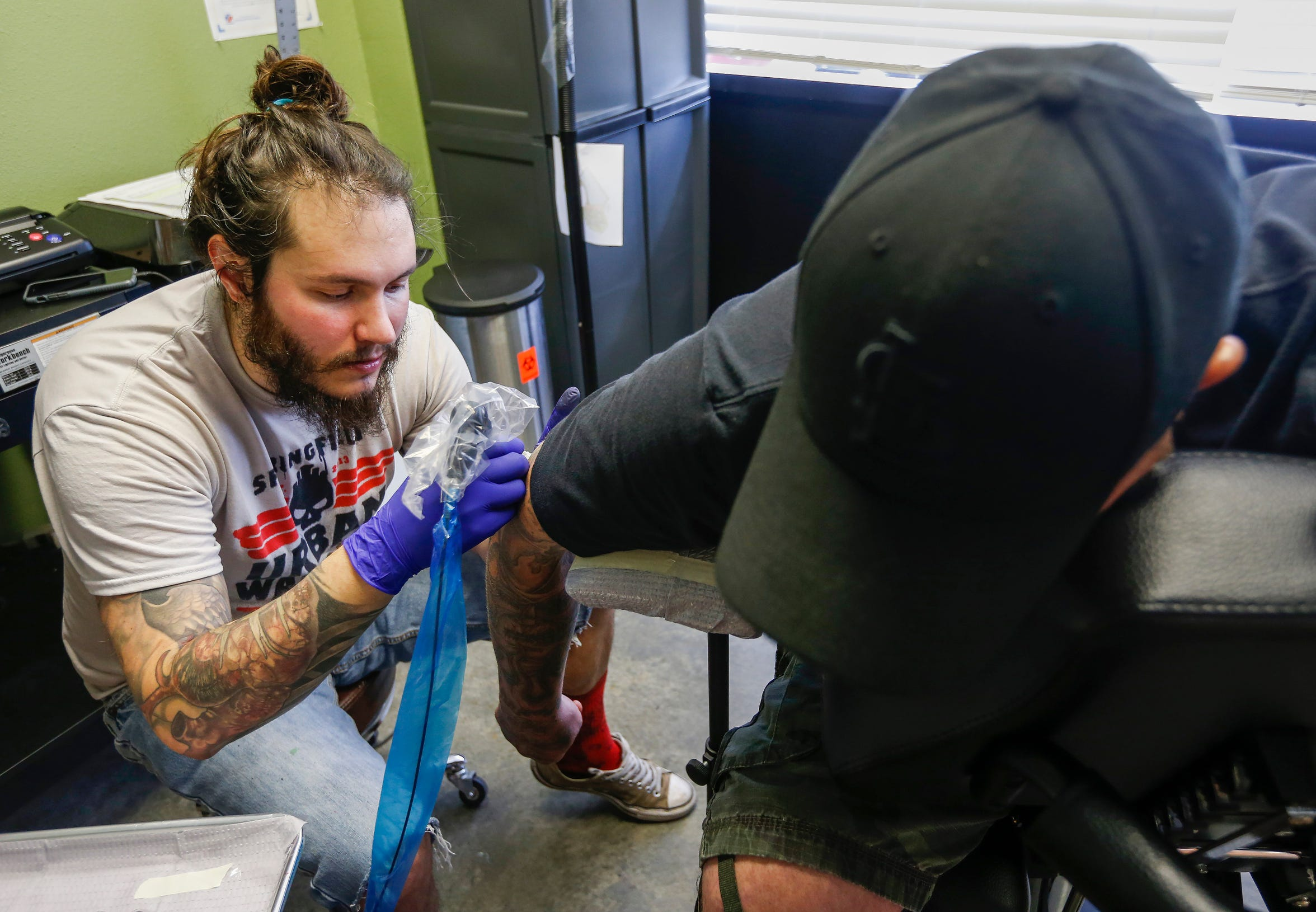 Justin Fleetwood, at tattoo artist at Queen City Tattoo Company, begins to cover up a Nazi SS bolt tattoo on the elbow of a man who wished not to be identified on Tuesday, Aug. 21, 2018. Fleetwood is offering to cover up people's hate-tattoos at no cost.