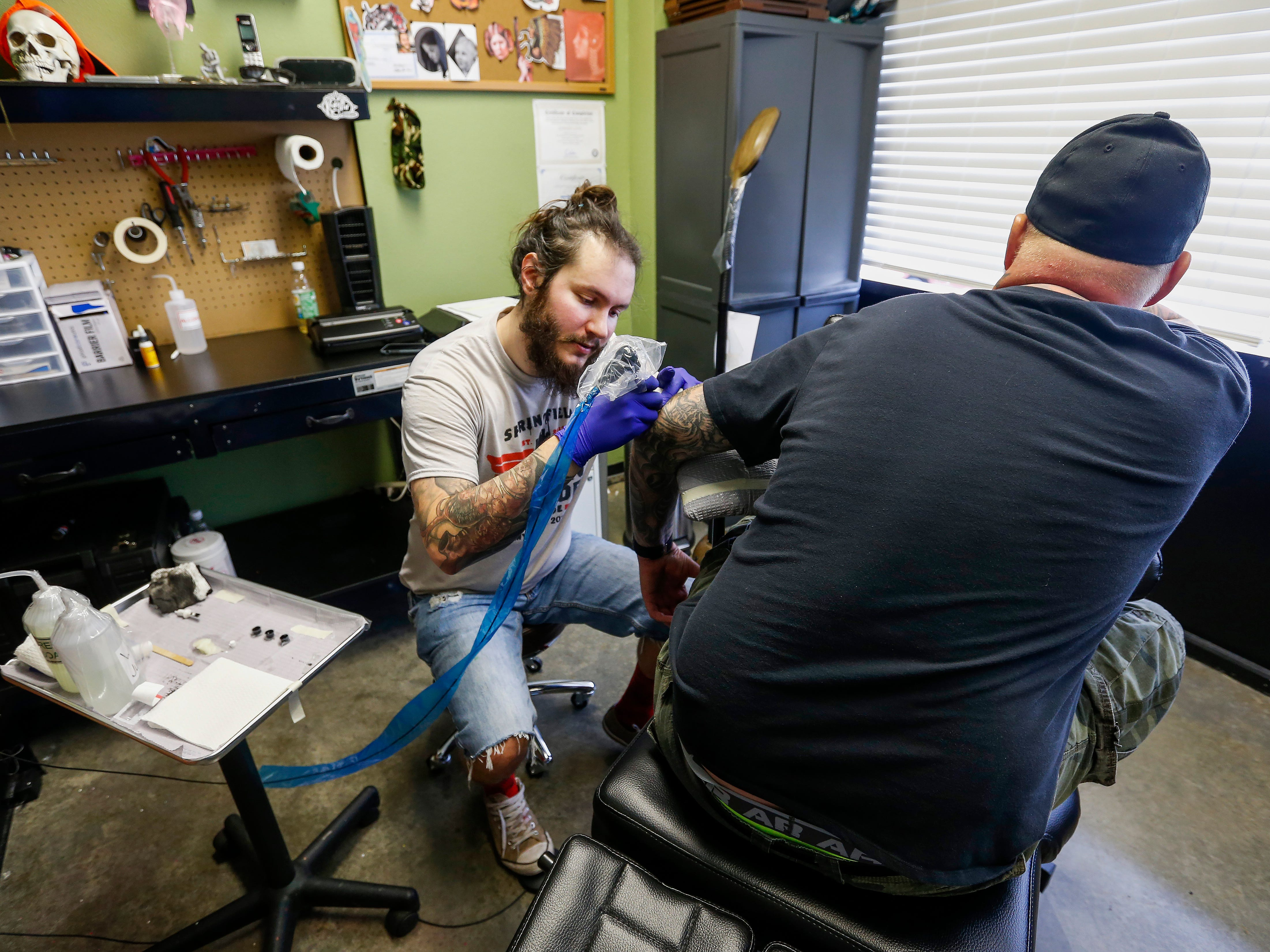 Justin Fleetwood, at tattoo artist at Queen City Tattoo Company, covers up a swastika tattoo on the elbow of a man who wished not to be identified on Tuesday, Aug. 21, 2018. Fleetwood is offering to cover up people's hate-tattoos at no cost.