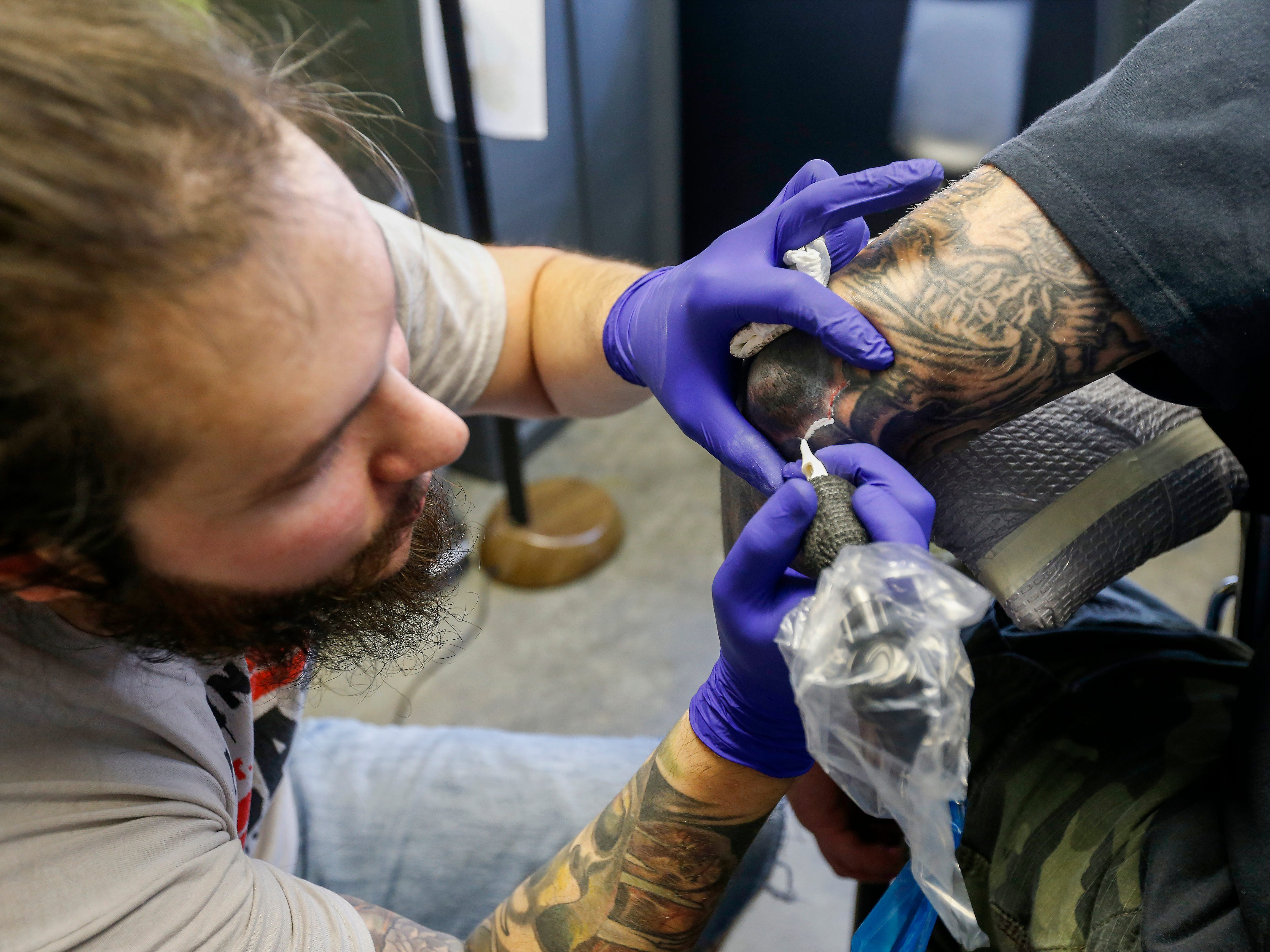 Justin Fleetwood, a tattoo artist at Queen City Tattoo Company, covers up a swastika tattoo on the elbow of a man who wished not to be identified on Tuesday, Aug. 21, 2018. Fleetwood is offering to cover up people's hate-tattoos at no cost.