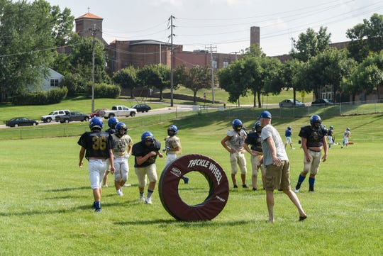 Players use a tackling dummy during practice on Rau Field Tuesday, Aug. 21, at Cathedral High School.
