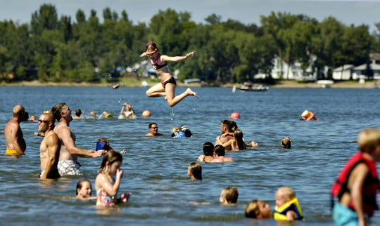 People flock to the beach at Lakeside Park in Big Lake to swim and relax in the sand as temperatures soared into the 90s in this file photo.