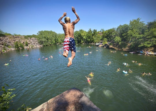 A diver takes flight from a cliff high over the 116-foot-deep water of Quarry 2 in Quarry Park & Nature Preserve in this file photo.