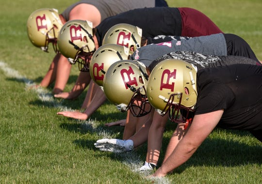 Players hit the grass while running through a drill during practice Wednesday, Aug. 15, at Royalton High School.