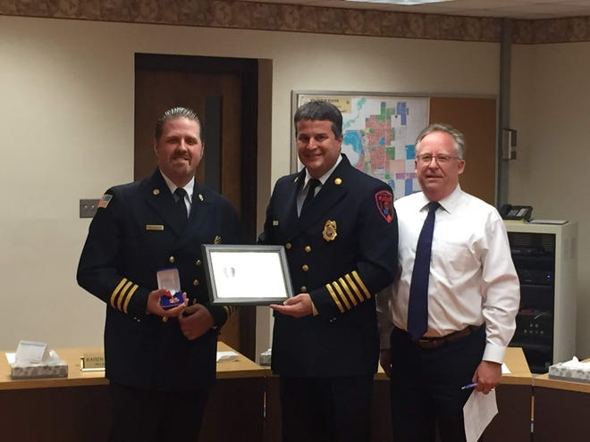 Plover Assistant Fire Chief Tom DeWitt (left) receives the medal of valor award from the Plover Fire Department for his role in saving a person's life during a February car fire while he was off duty.