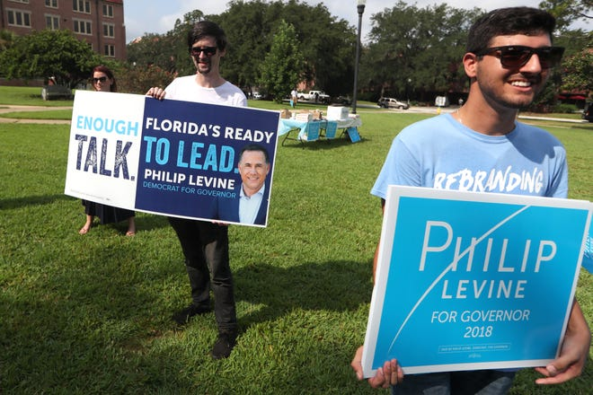 Gubernatorial candidate Philip Levine's staffers Ian Grossman, left, and Jeremy Cramarossa help the candidate campaign at Landis Green on FSU's campus Wednesday, Aug. 22, 2018.
