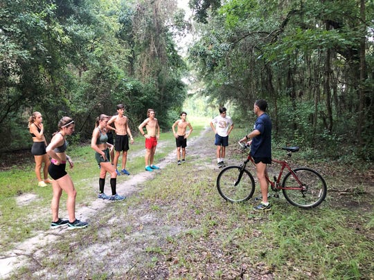 Coach Gary Droze talks with his runners during practice.  The TCC men and women will compete in a dual meet against Florida Gateway College on Aug. 24 at Phipps Park.