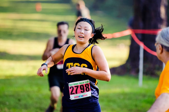 TCC's Mia Wiederkehr  crosses the finish line at during a meet.