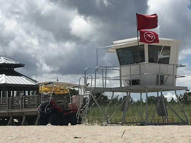 "A ""no swimming"" flag flies Wednesday, Aug. 22, 2018, at Bathtub Beach in Martin County, the day after the beach was closed to swimming because of possible blue-green algae."