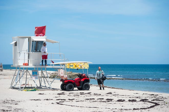 """Martin County Ocean Rescue lifeguard Joe Ryan (left) instructs Keith Fountain, of Port St. Lucie, not to swim in the ocean Wednesday, Aug. 22, 2018 at Bathtub Reef Beach in Martin County. Beachgoers were instructed to stay out of the water by a """"no swimming"""" flag flying from lifeguard stands since blue-green algae was spotted close to shore Tuesday at one of the county's most popular beaches, prompting officials to close the beach for swimming. """"I had no idea,"""" Fountain said."""