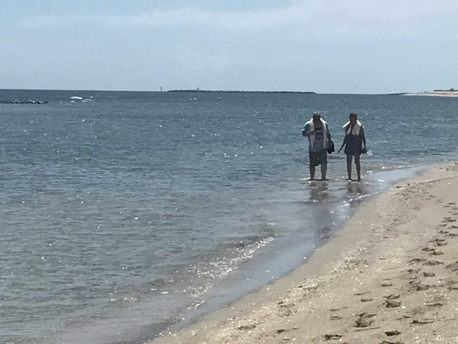 Joe and Gayle Rohn of Cedar Rapids, Iowa, walk Wednesday, Aug. 22, 2018, in the water at Bathtub Beach near Stuart, unaware a warning not to swim in the water because of possible blue-green algae had been issued.