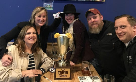 Trivia team members Joanne Blandford, Laurie K. Blandford, Brooke Dove, Patrick Dove and Stephen Davis celebrate their win with a trophy full of beer at Sailfish Brewing Company in Fort Pierce.