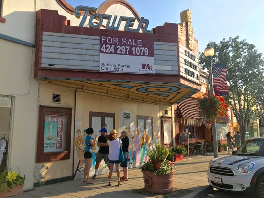 Community members chat outside the Tower Theater in downtown Santa Paula.