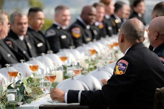 "Firefighters from Cal Fire and other entities await service of dishes by the red and blue teams during a ""MasterChef"" episode shot in Ventura County in March. The show honoring Thomas Fire personnel is scheduled to debut on Aug. 29."