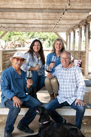 "Hitching Post Wines vintners Frank Ostini, front left, and Gray Hartley, front right, pose with family members Jami Ostini and Charlotte Hartley and winery dog Olive on the grounds of their new tasting room and picnic grounds in Buellton. The site is next to Hitching Post 2 restaurant, which played a starring role in the 2004 film ""Sideways."""