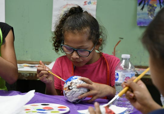 Clarissa, 6, paints her hand-made pencil holder during the Manuel F. Hernandez Community Center open house on Tuesday, August 21, 2018.