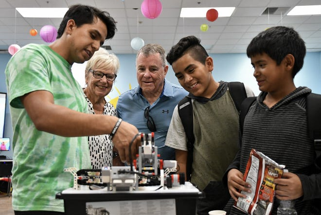 From Left: Pam Link, Bob Link, Joshua Pena and David Santamaria watch as Octavio Cortez demonstrates how a student-made Lego robot works at the Manuel F. Hernandez Community Center open house on Tuesday, August 21, 2018.