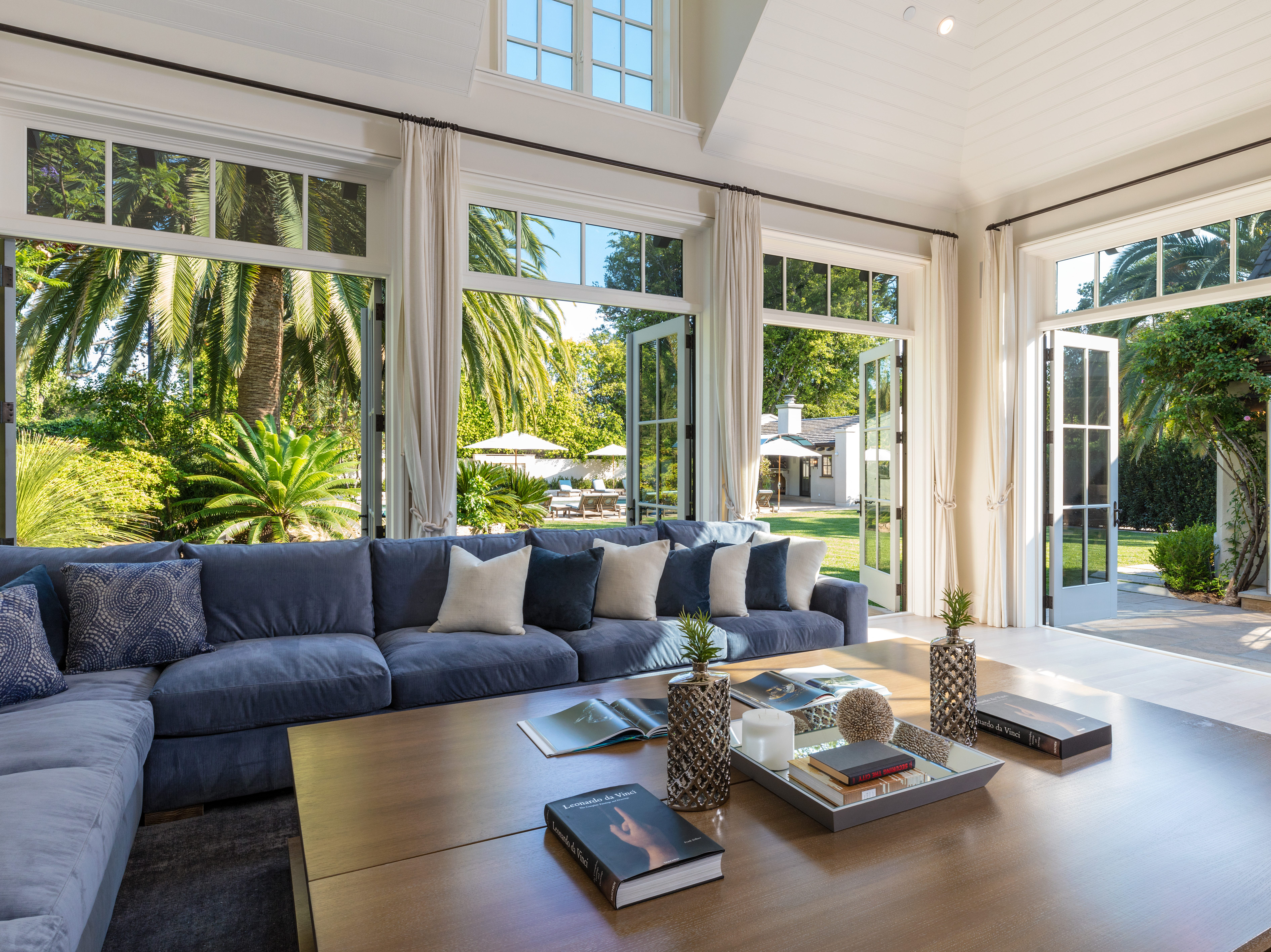 Designed to take full advantage of the climate for indoor-outdoor living, the bright sunny interior with its vaulted and beamed ceilings opens to a 60-foot pool and spa and a north-south tennis court on the mature landscaped grounds.