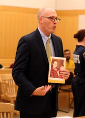 Prosecutor Jonathan Strongin holds a photo of Amanda Trenck as he addresses the court during the sentencing of Joseph Abraham at the Westchester County Courthouse in White Plains Aug. 22, 2018. Abraham was sentenced to 18 years to life in prison for stabbing his wife to death in their Yonkers apartment in 2017.