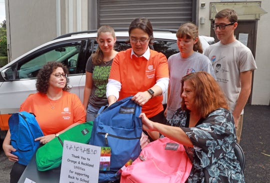 From left, Lisa Culhane of Orange & Rockland Utilities, volunteer Hope Casseles, Christina Ho of Orange & Rockland Utilities, volunteer Hannah Casseles, volunteer Thomas Casseles and Diane Elizabeth Serratore, Executive Director of People to People, check out a bag filled with school supplies at People to People in West Nyack Aug. 22, 2018. Orange and Rockland Utilities donated $10,000 toward People to People's Back to School with Dignity program, where backpacks are filled with school supplies for children from low-income households.