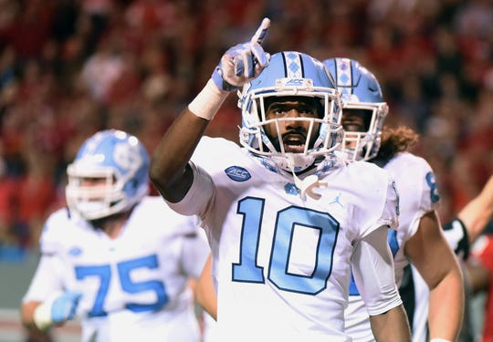 North Carolina Tar Heels receiver Jordan Cunningham (10) gestures to the crowd after scoring a touchdown during the second half against the North Carolina State Wolfpack at Carter-Finley Stadium.