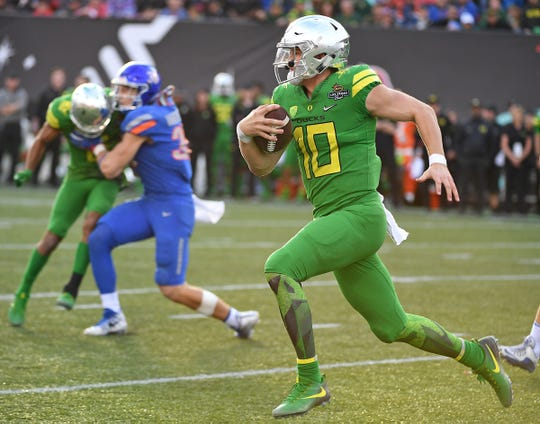 Oregon Ducks quarterback Justin Herbert (10) is flushed out of the pocket during the second half of play against the Boise Broncos in the 2017 Las Vegas Bowl at Sam Boyd Stadium.