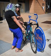Jeanette Perry of Downtown Wichita Falls Development demonstrates a new sculptural steel bicycle rack installed at the corner of 8th Street and Scott Avenue. Three more similar racks are being designed.