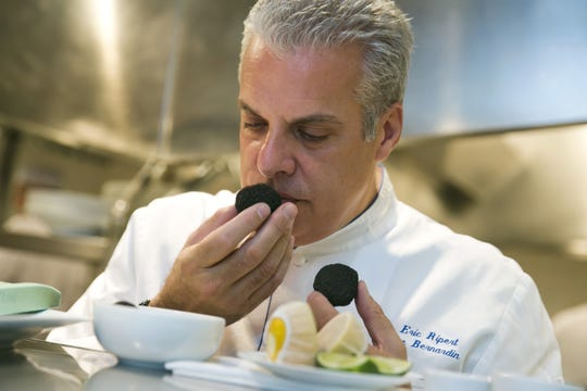 Richard Drew/AP Eric Ripert sniffs the truffles in the kitchen of his New York restaurant, Le Bernadin, before the lunch service.