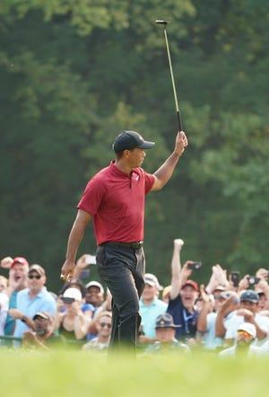 Tiger Woods celebrates after making a birdie putt on the 18th green during the final round of the PGA Championship golf tournament at Bellerive Country Club.