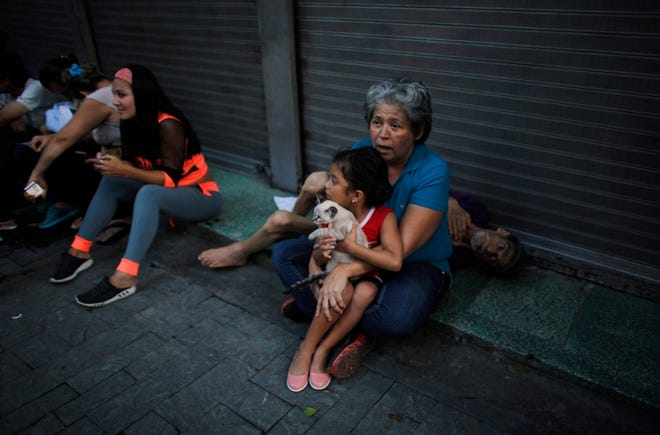 Maryeli Verde holds her niece Yalin, who clutches her cat Will, as Yalin's grandfather Tonisio, who is sick, lies behind them after they evacuated their apartment on the ninth floor after a powerful earthquake shook eastern Venezuela, causing buildings to be evacuated in the capital of Caracas.