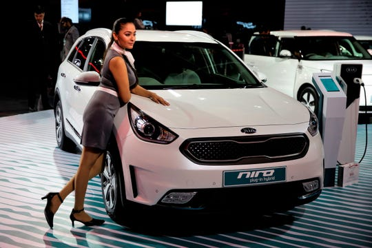 FILE- In this Feb. 7, 2018, file photo a model poses next to KIA motors' Niro electric hybrid car at the Auto Expo in Greater Noida, near New Delhi, India. Niro offers 50 mpg in combined driving. (AP Photo/Altaf Qadri, File)
