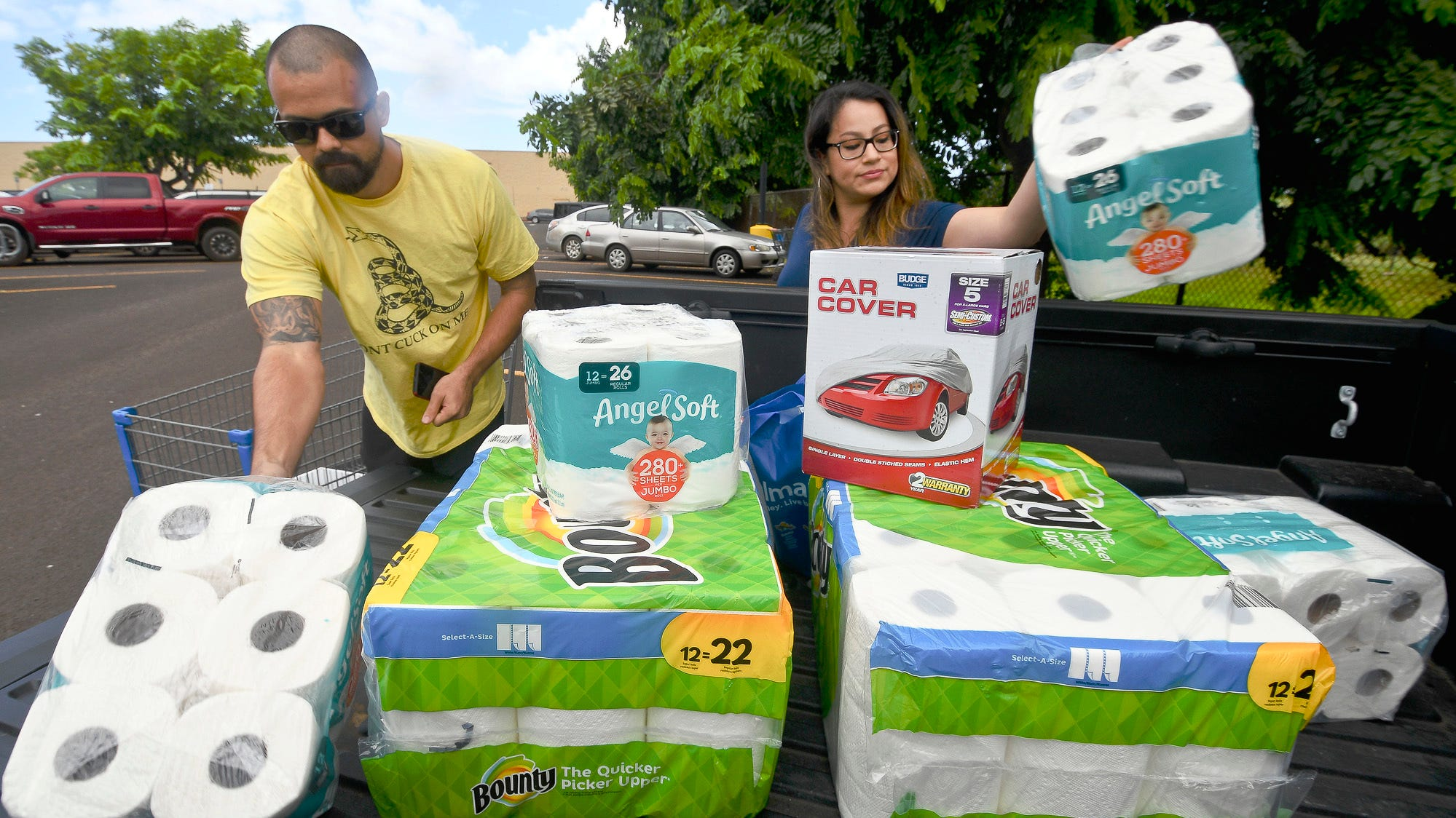 Bryce and Dom Boeder of Waimea, Kauai, load their truck with storm supplies in the parking lot of a Walmart store in Lihue, on the island of Kauai, Hawaii.