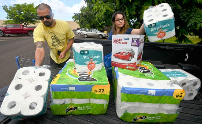 Bryce and Dom Boeder of Waimea, Kauai, load their truck with storm supplies in the parking lot of a Walmart store in Lihue, Hawaii.