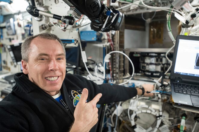 This April 11, 2018 photo provided by NASA shows astronaut Andrew Feustel conducting science operations using the Multi-Use Variable-G Platform that enables research into smaller and microscopic organisms at the International Space Station.