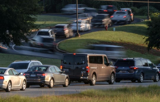 Cars leave after bringing children to Midway Elementary School in Anderson in August. The school has a long path for cars to get off Harriet Circle.