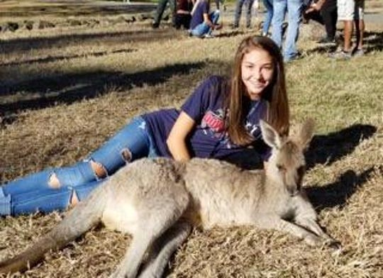 Morgan Roberts, a junior at Palmetto High School, next to a kangaroo at a wildlife sanctuary in Australia this summer. Roberts won two silver medals in cross country events competing in Australia.