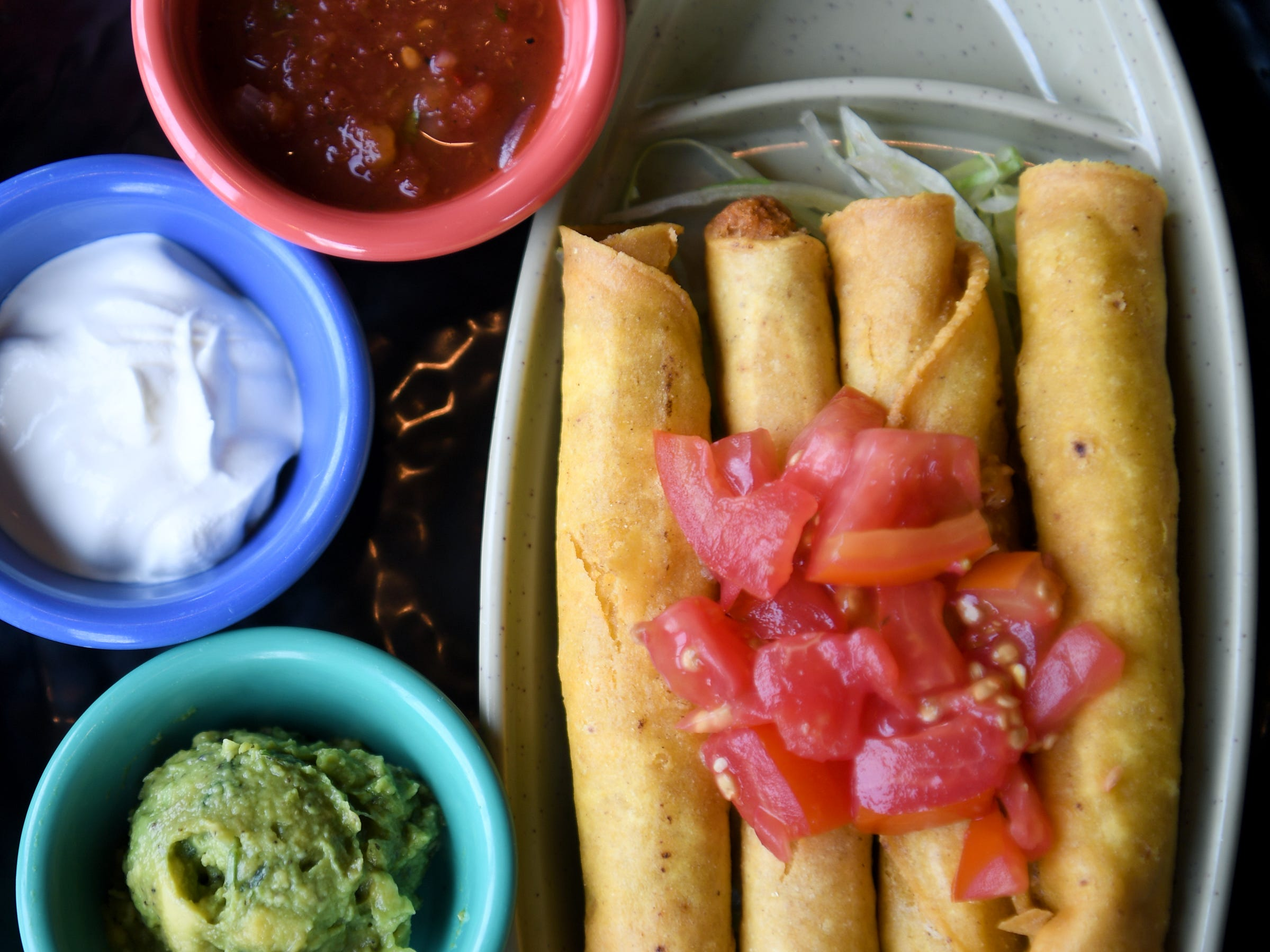 The chicken taquitos at Takosushi are served with homemade salsa, lettuce, tomato, guacamole and sour cream.
