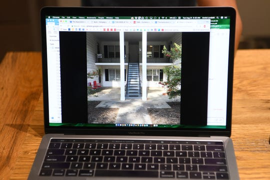 A photograph on Annie Lundahl's computer shows the run-down apartment complex in North Asheville that she and her wife bought, renovated and now live in before any construction began.