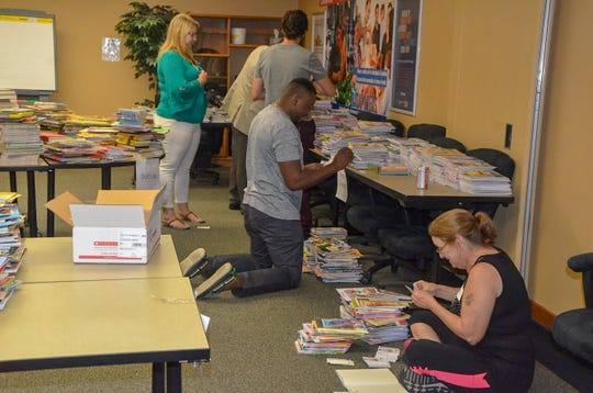 Volunteers for United Way of the Battle Creek and Kalamazoo Region spent the afternoon of Wednesday, Aug. 22, 2018, sorting donated books for local schools.