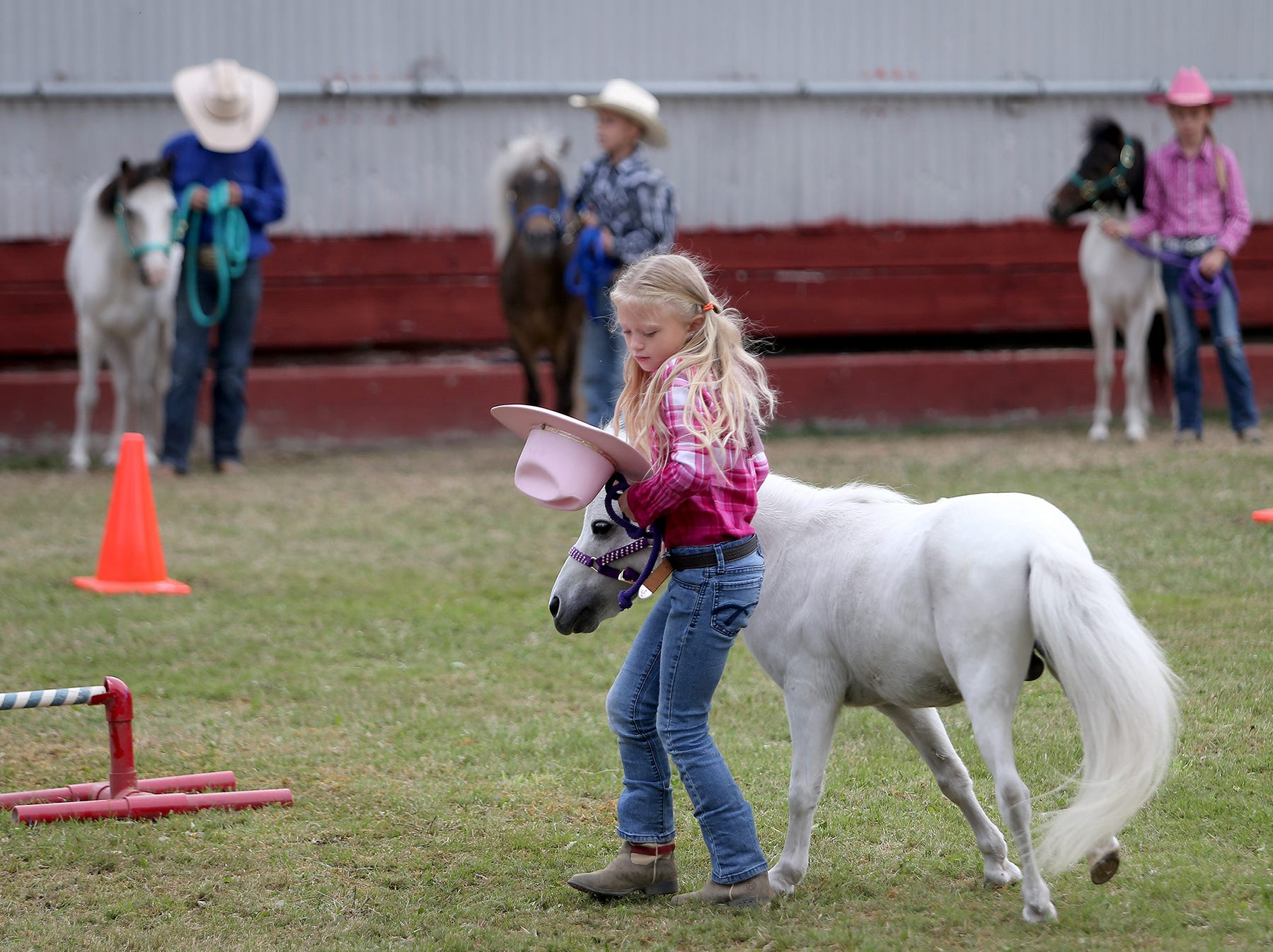 Holly Lowe loses her cowgirl hat as she runs with Spanky in the mini horse jumping open 10 & under amateur at the Kitsap County Fair & Stampede on Thursday, August 23, 2018, at the Kitsap County Fairgrounds.The fair goes from 10 a.m. until 10 p.m..