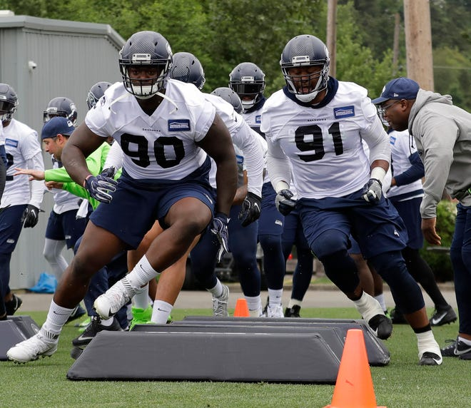 Seahawks defensive tackle Jarran Reed (90) and defensive tackle Tom Johnson (91) take part in an agility drill during a May practice in Renton.  When the Seahawks looked to bolster the interior of its defense in the offseason, it looked to Minnesota for the help. The Seahawks signed former Vikings defensive linemen Tom Johnson and Shamar Stephen.