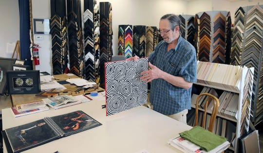 After 23 years in Seattle's Rainier Square, longtime Lemolo resident Jeffrey Moose has relocated his art gallery to Winslow Way in Bainbridge Island. He is putting on the hanging hardware in his frame shop. He specializes in aboriginal Australian art.