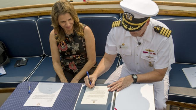 State Public Lands Commissioner Hilary Franz and Naval Base Kitsap commanding officer Capt. Alan Schrader sign a restrictive easement to protect habitat and buffer Navy operations along the eastern shore of Hood Canal.