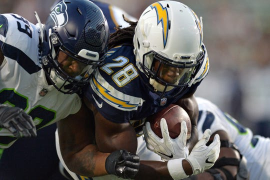 Seahawks cornerback Dontae Johnson, left, tackles Chargers running back Melvin Gordon during Saturday's game in San Diego. Johnson is competing with Byron Maxwell and rookie Tre Flowers to be Seattle's starting right cornerback.