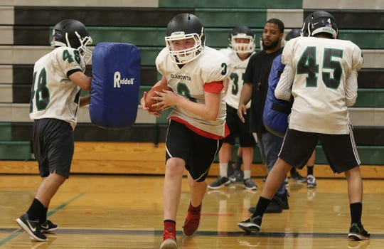 Klahowya's football players wore shoulder pads and helmets during a preseason practice inside the school's gymnasium.