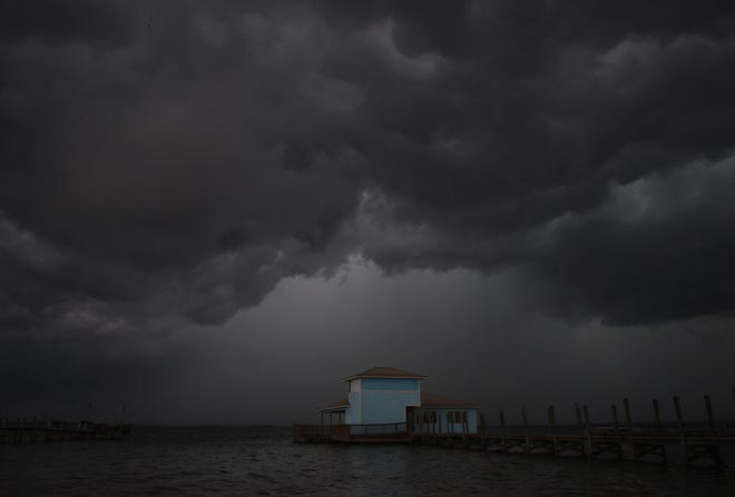 A vacant blue building sits on the Banana River in south Cocoa Beach, framed by approaching storm clouds from the west. The building, now damaged from Hurricane Matthew, was Fisherman's Wharf, once a popular seafood restaurant years ago.