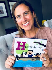 "Julie Beasley holds her book ""H is for Harvey."""
