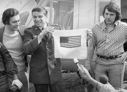 Col. John Dramesi of Blackwood, center, holds a flag he made while in a prison camp during the Vietnam War, as he stands with his brothers Leonard, left, and Richard, right, in 1973.
