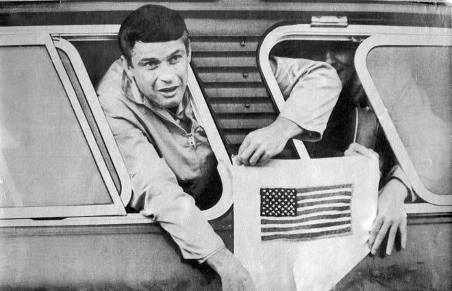 "Blackwood's Lt. Col. John Dramesi, a Vietnam War POW,  gets a helping hand as he hangs his handmade American flag out the windows of a bus en route to Clark Air Base hospital in the Philippines  in 1973 after he and other POWS  were freed by North Vietnam from the ""Hanoi Hilton"" prison. He will be buried next month in Arlington National Cemetery."